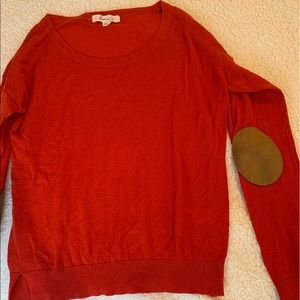 Red-orange sweater with elbow patches